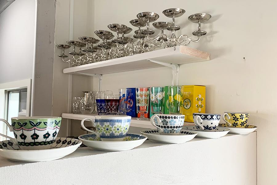 オープンキッチンの棚にプリン用のスタンドが並ぶ。レトロなグラスやカップも魅力的